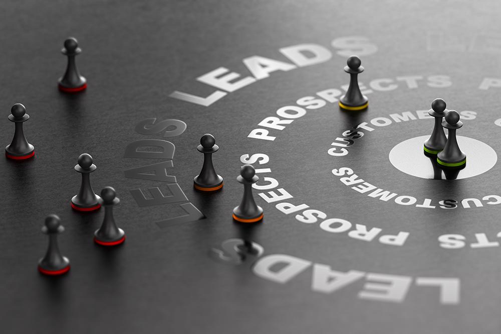 """Peças de xadrez sobre um tabuleiro preto com palavras como """"leads, prospecções e clientes"""". Representa o uso de estratégias para atrair clientes."""