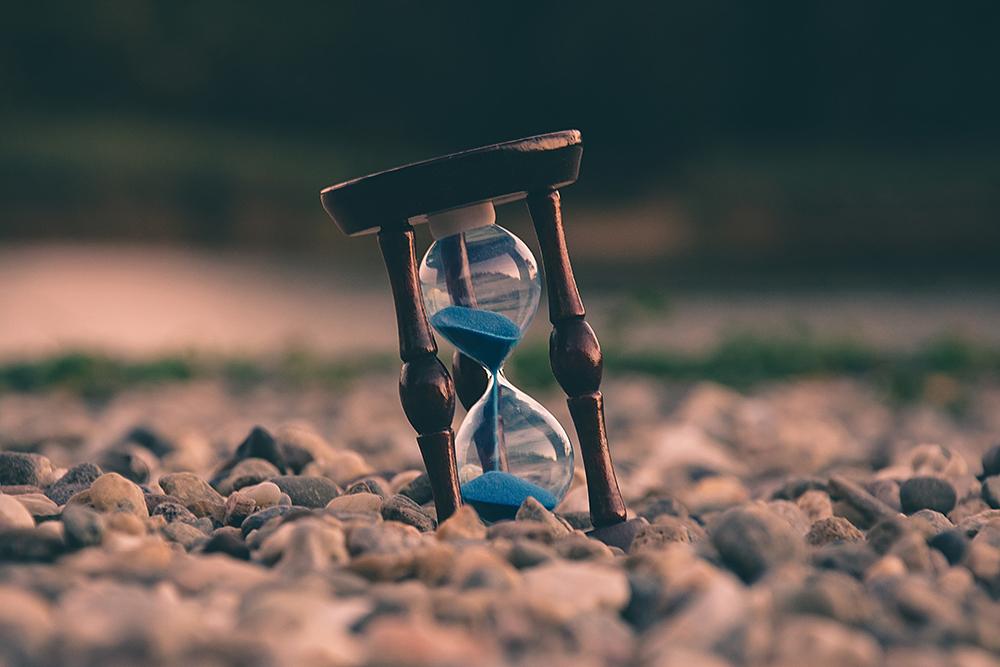 A foto mostra um solo de pedras com uma ampulheta com areia escorrendo de cima para baixo. Representa a gestão de tempo na advocacia.