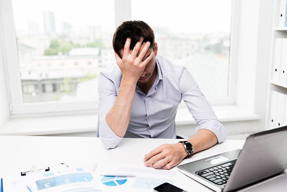 Advogado sentado em frente a um notebook com semblante preocupado e com a mão na testa, representando dificuldades enfrentadas em uma Crise financeira na advocacia