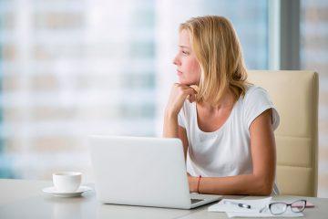 Uma advogada sentada à sua mesa olhando pela janela com semblante entediado. Representa a monotonia que a advocacia ultrapassada pode trazer.