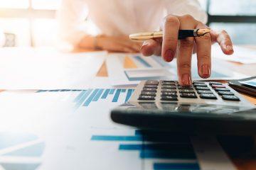 A imagem foca na mão de uma advogada apertando as teclas de uma calculadora enquanto analisa alguns gráficos. Representa o controle financeiro em Escritórios de Advocacia