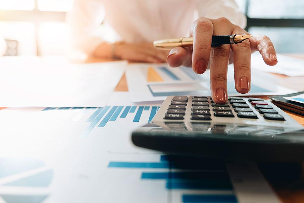 A imagem foca na mão de uma advogada apertando as teclas de uma calculadora enquanto analisa alguns gráficos. Representa o controle financeiro em Escritórios de Advocacia Gestão financeira na Advocacia