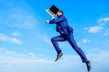 Um advogado com um notebook na mão saltando com um céu azul de paisagem ao fundo. Representa a satisfação do advogado ao trabalhar na área do direito que realmente gosta