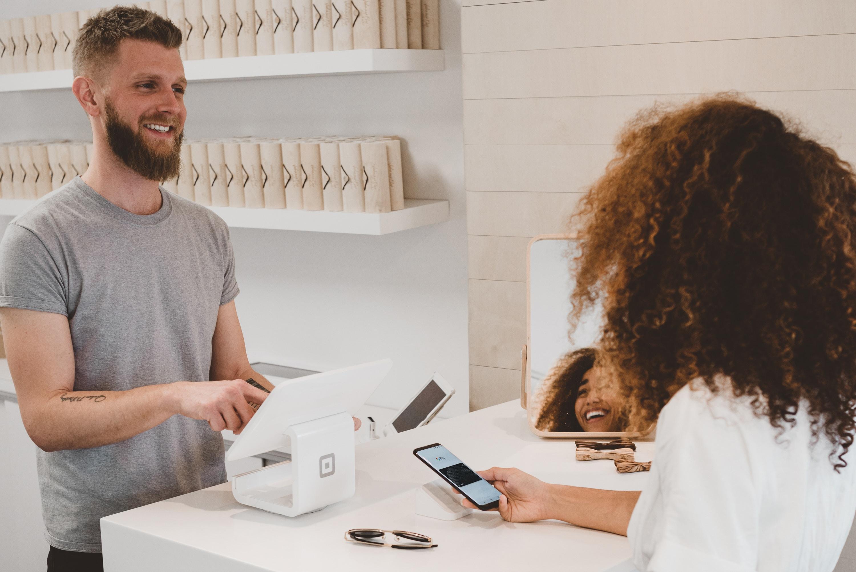 A imagem mostra um homem comprando produtos de uma mulher em um balcão. O direito do consumidor é fundamental para garantir práticas de consumo justas e adequadas para quem consome.