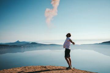 Advogado no topo de uma montanha com braços abertos representando liberdade. Ao fundo, uma paisagem bonita com outras montanhas e um lago.