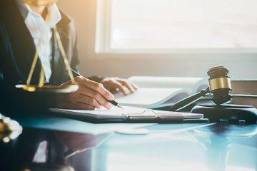 A foto mostra as mãos de um advogado trabalhando com documentos em uma mesa de escritório.