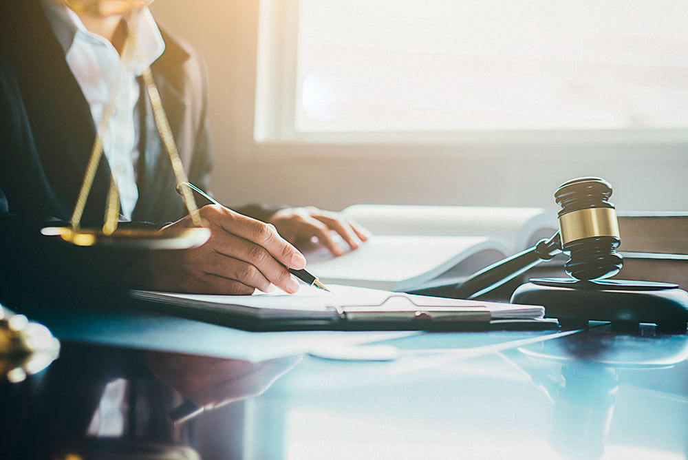 A foto mostra as mãos de um advogado trabalhando com documentos em uma mesa de escritório. Saiba mais sobre o cumprimento de sentença.