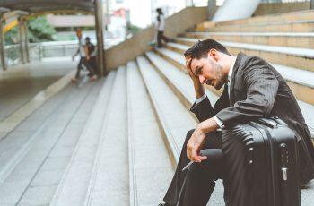 Um advogado sentado em uma escadaria com semblante preocupado e sobrecarregado