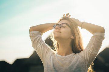 Imagem de uma mulher relaxando ao ar livre, de olhos fechados e braços descansados. A gestão de escritórios de advocacia não precisa ser estressante.