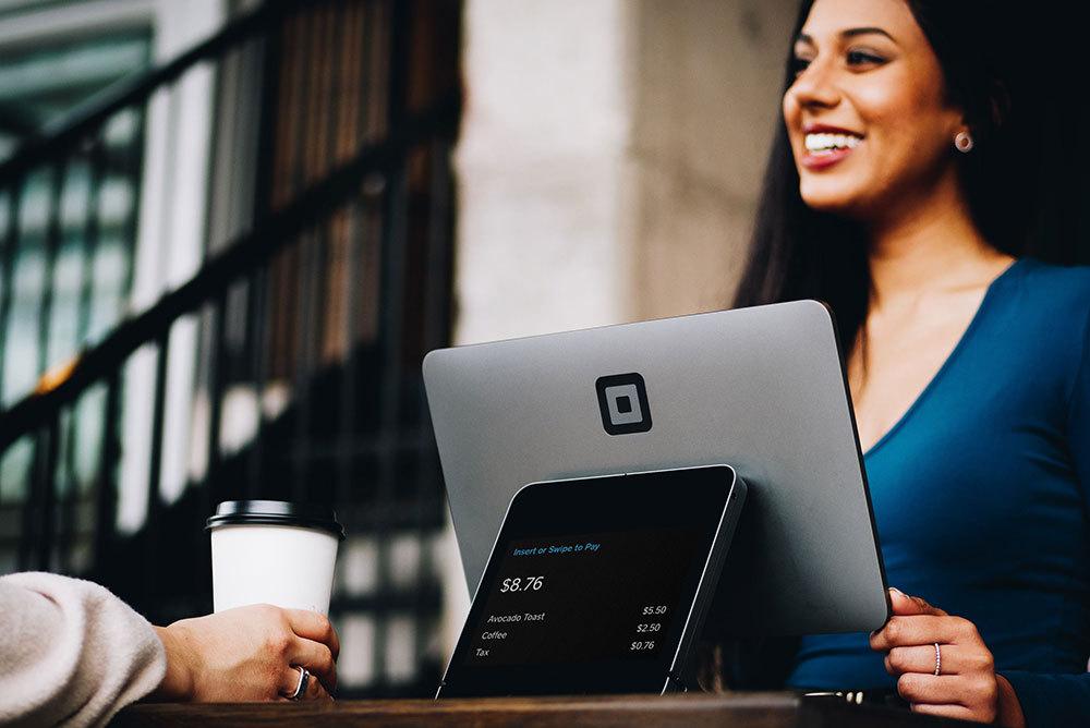 A foto mostra uma advogada atendendo um cliente enquanto este toma um café. Ilustra bem o processo de como captar clientes na advocacia.