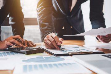 Dois advogados assinam e leem papéis em uma mesa de escritório, onde planejam e realizam suas tarefas de compliance jurídico.